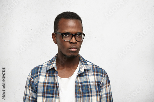 Photo  Studio shot of suspicious young African American hipster wearing stylish glasses frowning, looking at camera with distrust