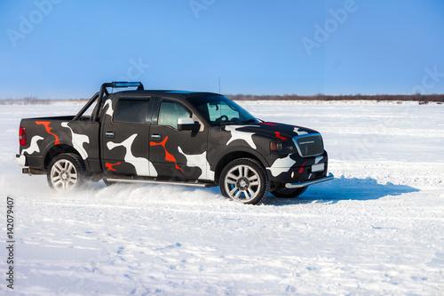 фотография  Black truck moving fast on snow