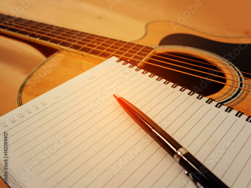 Guitar with notebook for composing on table. Canvas Print