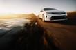 White modern car drive at asphalt road at sunset