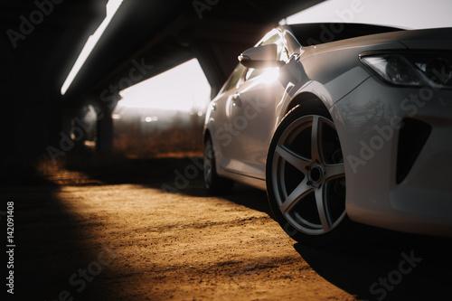 Obrazy na płótnie Canvas White modern car on the road at sunset