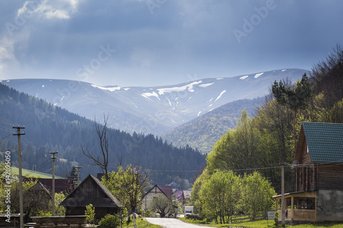 Fotobehang Fantasie Landschap Road in the village along the houses on background of the mountains. Spring dawn in the Carpathians