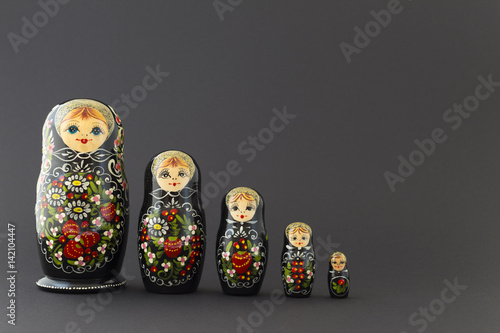 Tableau sur Toile Beautiful black matryoshka dolls with white, green and red painting in front of