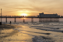 Photographer Shooting The Sun As It Rises Behind Worthing Pier