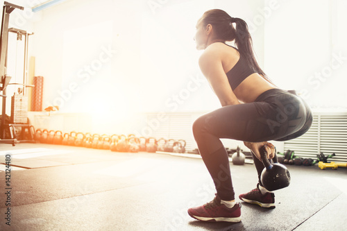 Fotografie, Obraz  Athletic woman exercising with kettle bell while being in squat position