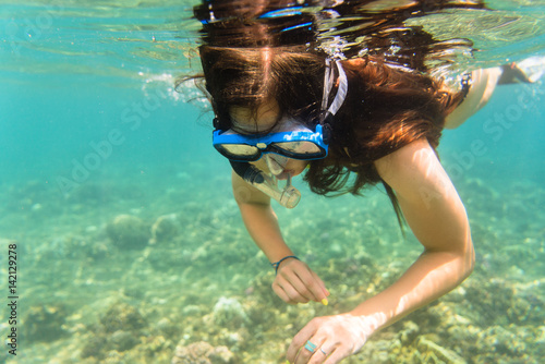 Fototapeta Girl in bikini snorkelling in tropical sea obraz na płótnie