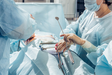 Surgeon wearing gloves operates women's breasts . Operation close up.