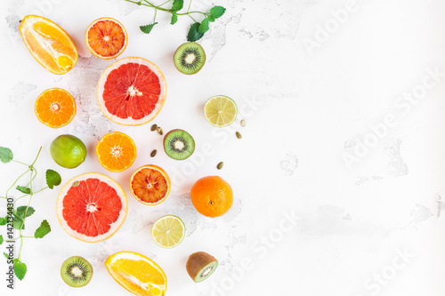 Fruit background. Colorful fresh fruit on white table. Orange, tangerine, lime, kiwi, grapefruit. Flat lay, top view, copy space