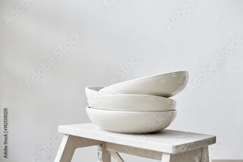 Fotomural Samples handmade ceramic white plates on wooden table, working process in studio