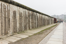 Tourists Taking Pictures At The Berlin Wall Memorial In Germany. Writing Is Visible On The Cement Wall. Two Sides Of The Wall - East And West Berlin.