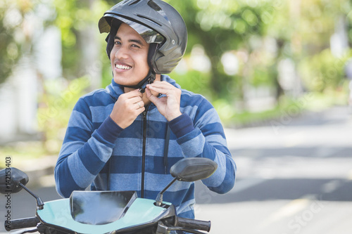Photo  man fastening his motorbike helmet