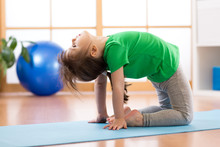 Child Girl Performing Frog Sportive Execrcise In Gym