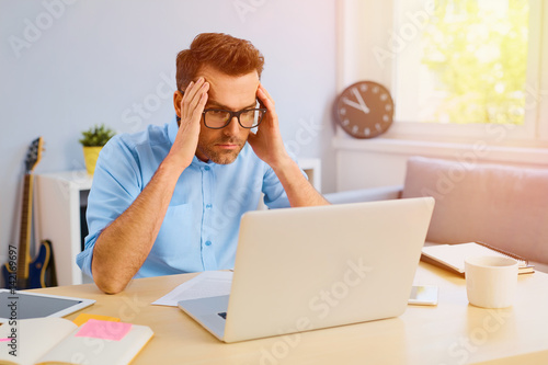 Photo  Worried man reading bed news on his laptop