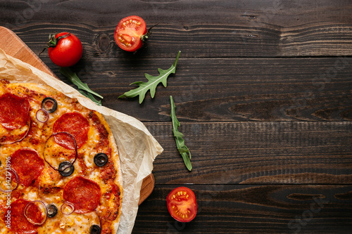 Spoed Foto op Canvas Pizzeria Delisious pepperoni pizza on the wooden table with copy space, top view