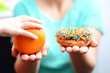 Educate children to choose healthy food concept with little girl choice to eat fruit, not a donut