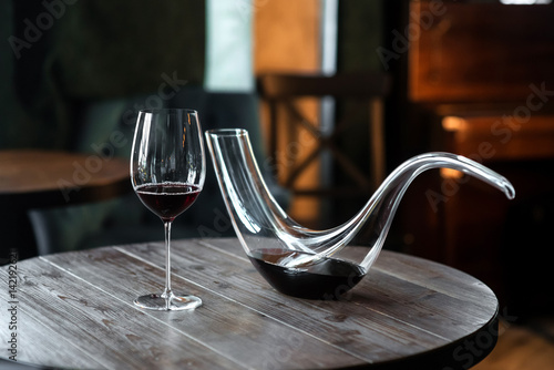 Photo Decanter with red wine and glass on wooden table in interior