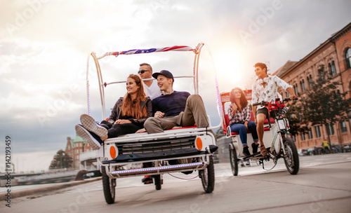 Fototapeta Young people enjoying tricycle ride in the city