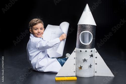 maly-chlopiec-z-papierowa-rakieta-na-czarnym-tle
