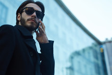 Low Angle Portrait Of Handsome Modern Man Wearing Sunglasses And Black Coat Making Phone Call Outdoors In Streets Of Business City