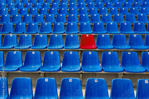 Dark blue rows of seats on the stadium. One red seat. Poster