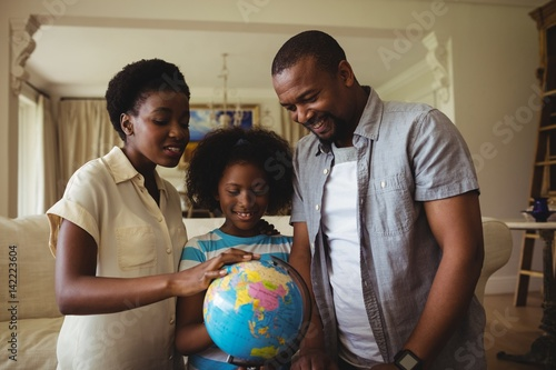 Parents and daughter looking at globe in living room Canvas Print