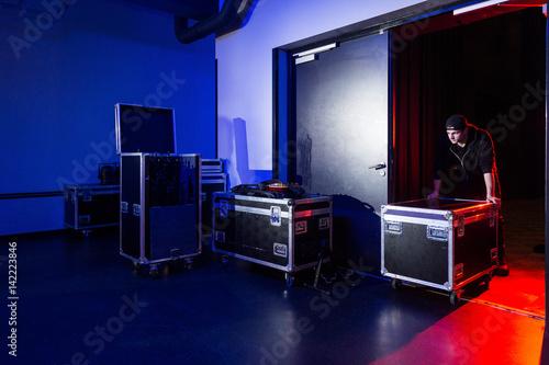 Roadie rolling a flightcase off the stage