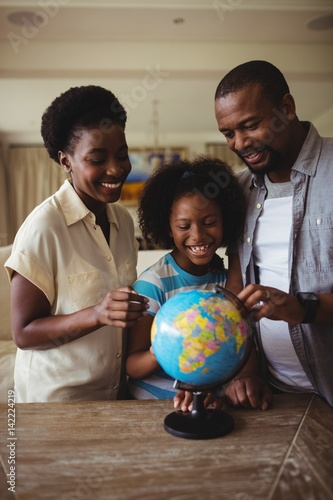 Parents and daughter looking at globe in living room Wallpaper Mural