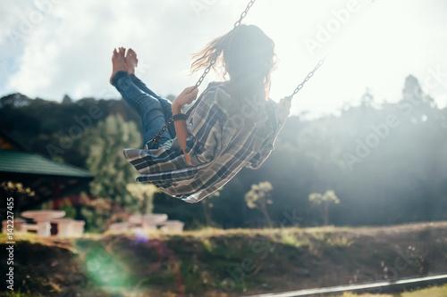 Happy barefoot girl on swing in sun light