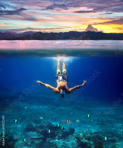Fotografía  Underwater shoot of a young man snorkeling in a tropical sea and colorful sunset