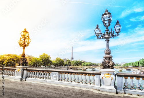 Papiers peints Paris Alexandre III bridge over the river Seine with the Eiffel tower in the background in Paris, France. Decorative lamp at foreground. Dramatic sky at background with opposite colors - yellow and blue.