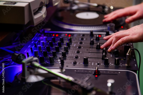 close up dj hands on equipment deck and mixer with vinyl record at