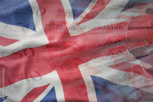 Leinwand Poster colorful waving national flag of great britain on a pounds money banknotes background