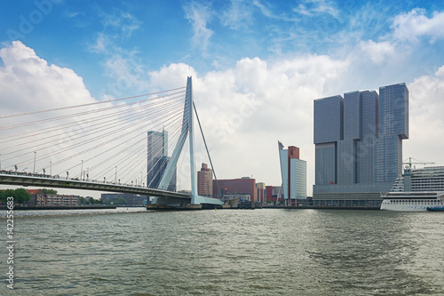 Staande foto Rotterdam Erasmus bridge and for the building the Rotterdam along the Wilhelminakade has the AIDA cruise ship docked.
