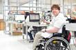 canvas print picture - Rollstuhlfahrer am Arbeitsplatz in einer Fabrik zur Montage von Elektronik - Alltag mit Gehbehinderung // Wheelchair driver at the workplace in the industry