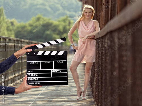 Fototapeta Clapperboard sign hold by female hands.