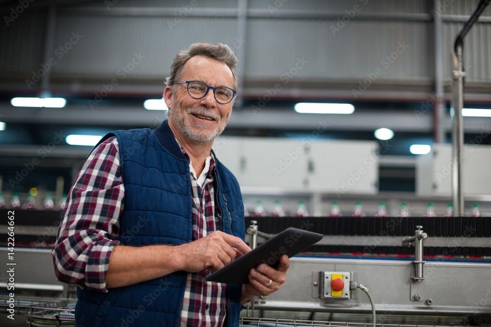 Fototapeta Smiling factory worker using digital tablet in the factory