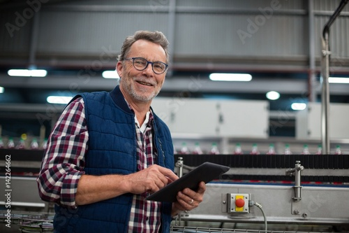 Obraz Smiling factory worker using digital tablet in the factory - fototapety do salonu