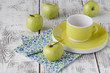 Fresh green apples in a dish on a rustic background.