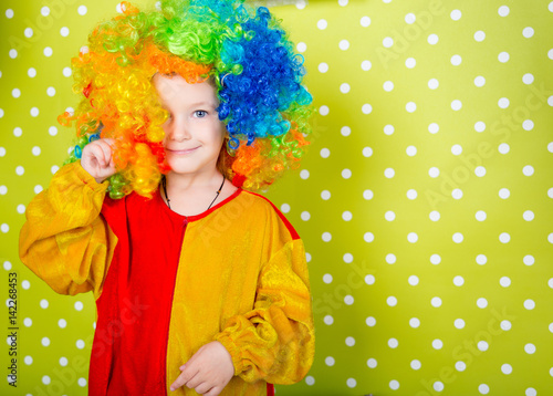 Fotografie, Obraz A cheerful clown in an iridescent wig and huge boots stands on a luscious bright