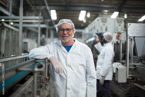 Fotografie, Tablou Smiling factory worker standing next to production line
