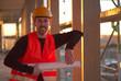 Freundlich lächelnder Mann mit Helm auf einer Baustelle