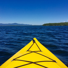 Bow Of Yellow Kayak On Choppy Lake On A Summer Day