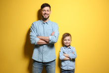 Handsome Man With His Son On Color Background