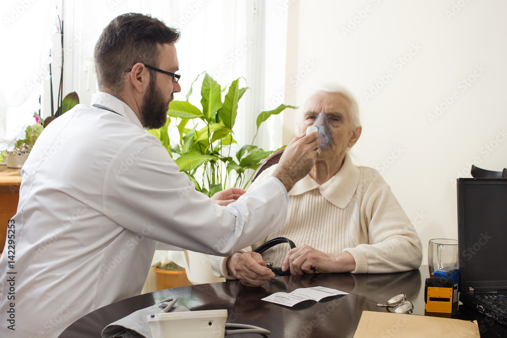 Fototapeta Lekarz trzyma inhalator przy twarzy starej kobiety. Atak astmy. Inhalacja górnych dróg oddechowych.  Lekarz w gabinecie przeprowadza inhalację.