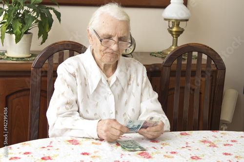 Fototapeta Staruszka liczy pieniądze siedząc przy stole. Emerytura. Stara kobieta liczy pieniądze. obraz