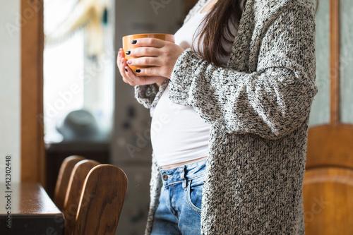 Fotografie, Obraz  A young pregnant woman holding a cup, close-up