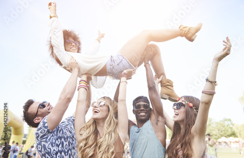 Excited woman crowd surfing at music festival - 142326294