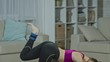 Tilt down of young woman in sports bra and leggings doing kneeling bent leg lifts on the floor in living room