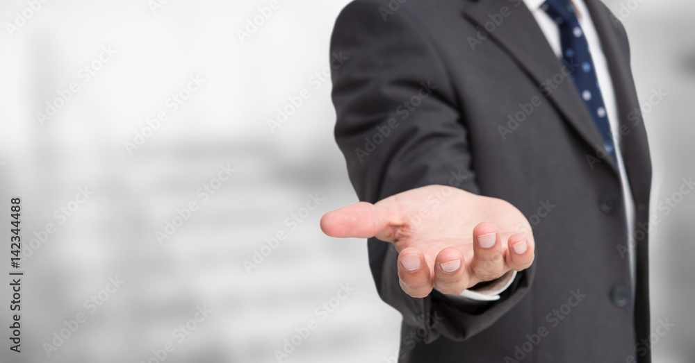 Fototapeta Business man mid section with hand out against blurry grey stairs