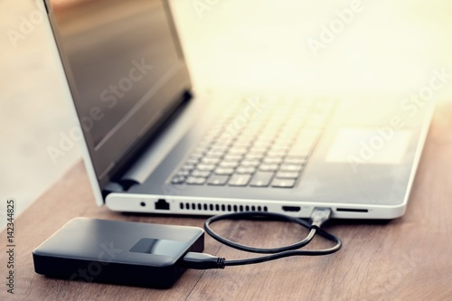 Technology concept : External hard disk and laptop computer